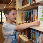 Elementary student pulls a book off a library shelf