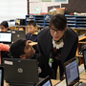 Student looking at teacher who is helping him with computer work